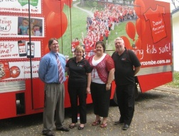 Bruce  and Denise Morcombe and the Administration Team posing in front of the red truck
